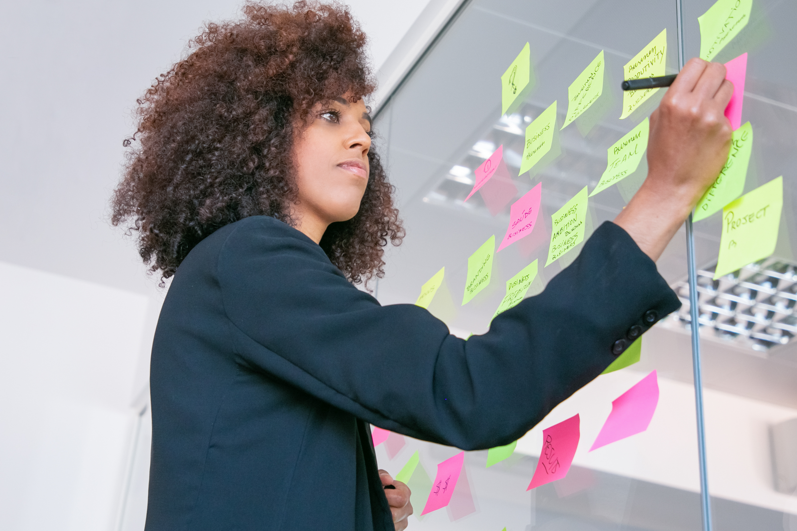 successful-pretty-businesswoman-writing-on-sticker-with-marker-thoughtful-confident-curly-female-manager-sharing-idea-for-project-and-making-note-brainstorming-business-and-training-c